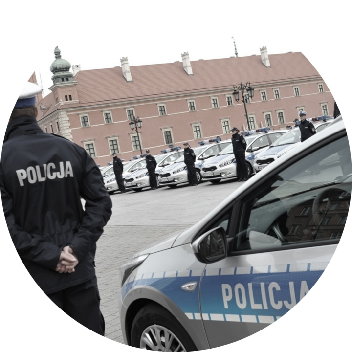 policeman and police car in front of the Royal Castle in Warsaw at day